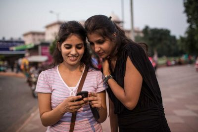 Two women look at a cell phone, India. Photo: Conor Ashleigh