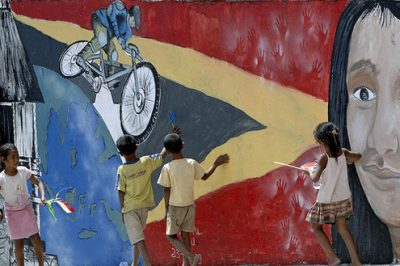 Children Playing in Front of Mural Promoting Tour-de-Timor Cycle Race