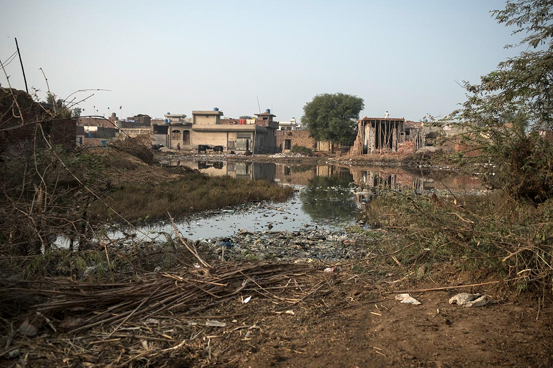 The picture shows a stagnant pool of polluted water near buildings in Pakistan