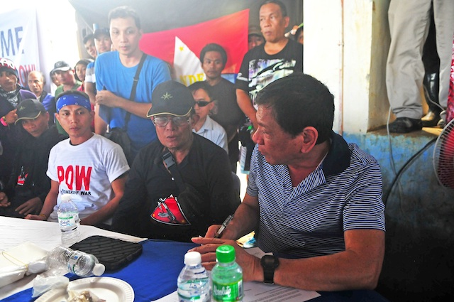 Rodrigo Duterte (right) receives Army Sgt. Adriano Bingil (left, in white shirt) from the New Peoples Army in Barangay Durian, Las Nieves, Agusan del Norte on New Year's eve, Dec. 31, 2015. Bingil was released after 104 days in captivity. MindaNews photo by Froilan Gallardo