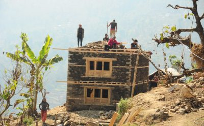 Reconstruction of a house in Nele VDC. Most of the earthquake-affected districts lie in the hilly and mountain regions with very poor to no road networks.