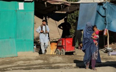 A woman walks with her child on a street in Afghanistan