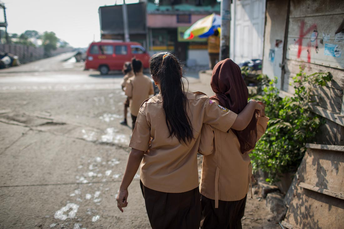 Two girls walk to school in North Jakarta.