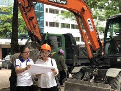 Two young women check blueprints in front of construction equipment