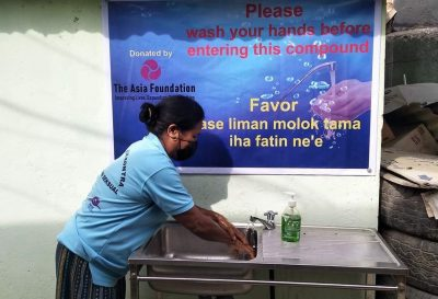 woman in face mask washes her hand in front of banner that encourages handwashing