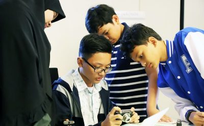 a woman in hijab and three boys review images on digital camera