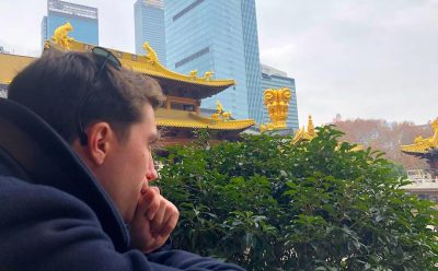 young man in contemplative pose in front of pagoda roofs