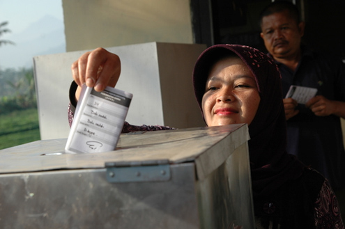 A woman inserts a ballot during Indonesia's elections