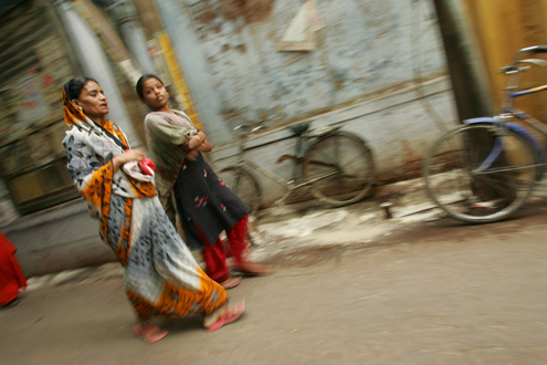 Women walk along a street in India.
