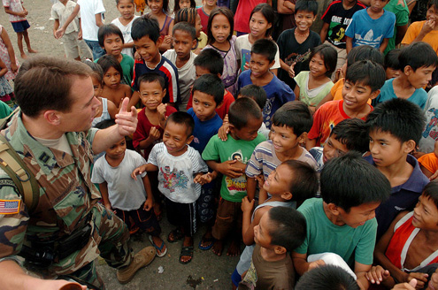 A U.S. army captain greets children in the Philippines