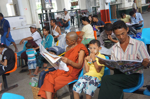 Burmese read newspapers while waiting for the bus.
