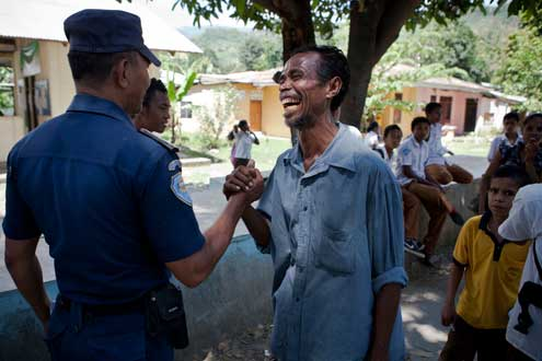 A community police officer walks through Becora talking to community members. With limited resources and training, Timor's police service faces the challenge of moving from a crisis response and public order orientation to helping to prevent disputes from escalating. A nascent community policing program is helping to address these challenges. Photo/Conor Ashleigh