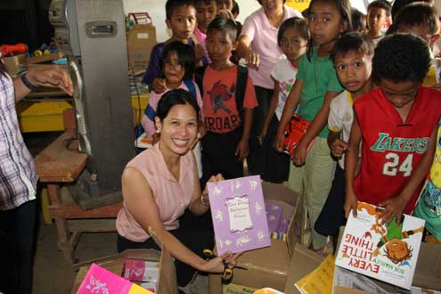 Anna Bantug-Herrera presents storybooks to Basper Elementary School students in Tacloban.