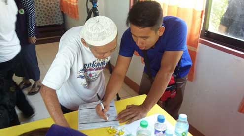 An elderly MILF supporter is assisted in filling out a voter's registration form during the registration of MILF central committee members and supporters in Maguindanao on March 7.