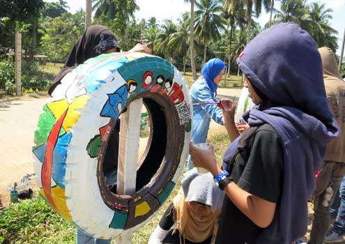 The event attracted young artists from the area who showcased their talents in a variety of forms, including tire painting, above, to promote messages of peace and unity.