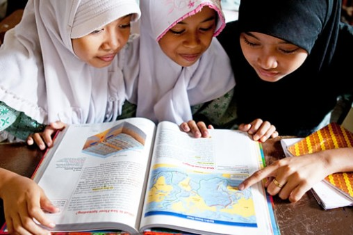 Students at a community learning center in Jakarta pore over a brand-new textbook provided by Books for Asia